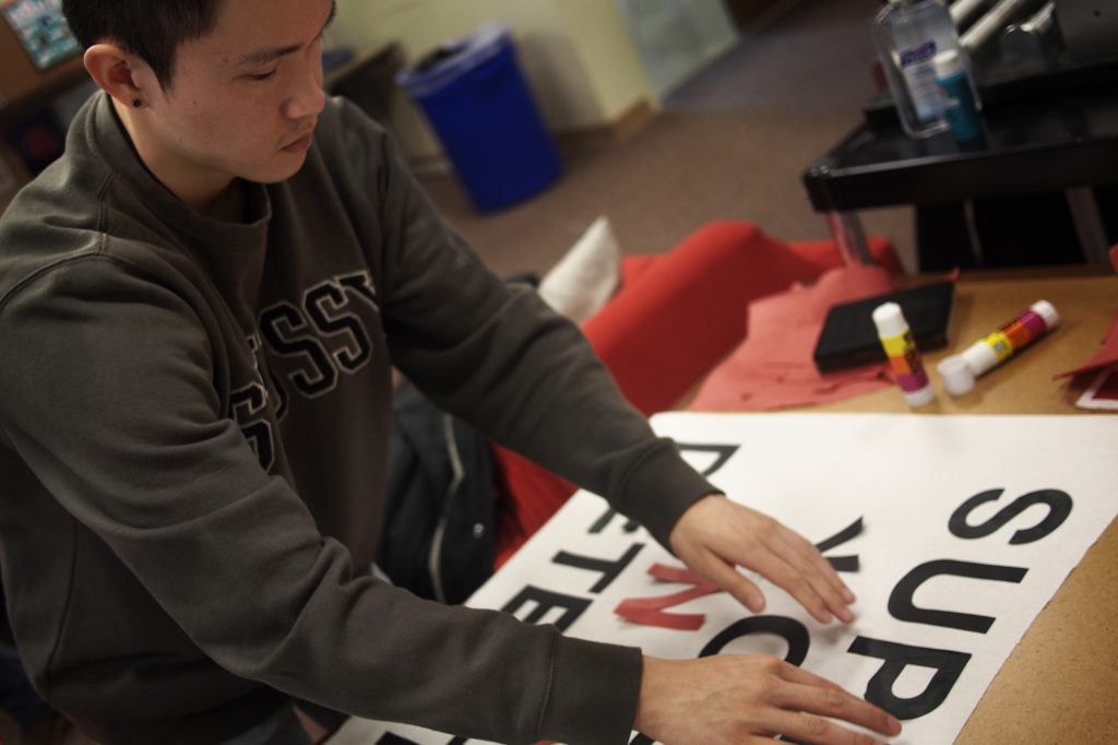 """Troy Osaki lays out his sign, which reads """"SUPPORT YOUTH NOT DETENTION"""" in support of a King County ordinance ensuring legal counsel for detained youth. Seattle University, April 24, 2017. (Quincy Surasmith/NextGenRadio)"""